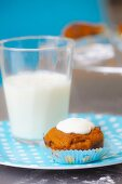 Carrot muffin with glacé icing and a glass of milk