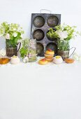 Mini cakes and confectionery in front of an old baking tray and vases of flowers