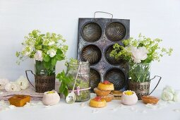 Mini cakes and confectionery in front of an old baking tin and vases of flowers