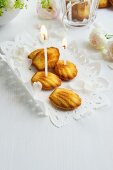 Madeleines on a doily decorated with birthday candles