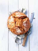 A rustic loaf on a tea towel with a bread knife