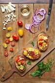 Red and yellow grape tomato bruschetta with red onions and mozzarella