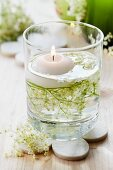 Floating candle and elderberry flowers in glass
