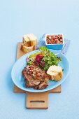 Lamb chop with salsa, salad and chunks of baguette