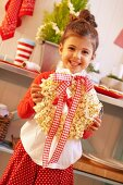 A small girl holding a Christmas wreath made from popcorn