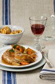 Veal shin with vegetables and a glass of red wine