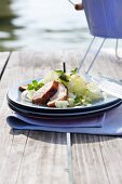 Grilled pork with cucumber and kohlrabi ribbons on a landing stage