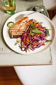 Salmon steak and a cabbage and coleslaw salad