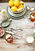 A view onto a wooden table with a bowl of lemons, iced teas and cutlery