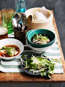 Broth with rice noodle rolls and bean sprouts