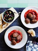Mondeghili (meatballs from Milan) in tomato sauce with a dish of black olives