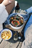 A pot of muscles in a chilli and tomato broth and a bowl of chips on a wooden jetty between a couple