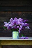 A bouquet of purple lilac in a milk can