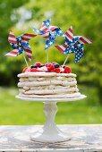 Meringue layer cake with berries and US-flag pinwheels