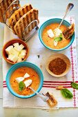 Cold yellow tomato soup with mozzarella and toast