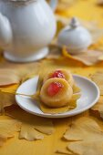 Mini sponge cakes with glacé cherries on gingko leaves