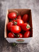 Small plum tomatoes in a cardboard box
