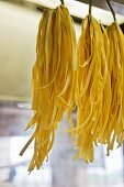 Bunches of tagliatelle hung up on large hooks to dry