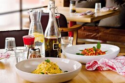 Two pasta dishes in deep bowls with a carafe of water and a bottle of olive oil, on a small table in a simple restaurant