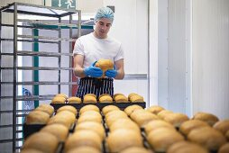 A baker checking the quality of freshly baked bread rolls