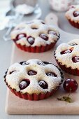 Mini cherry cakes in red baking dishes on a wooden board