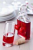 Cherry liqueur in a small bottle decorated with a fake cherry, some poured into a glass