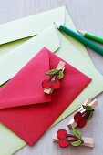 Colourful envelopes decorated with clothes pegs with cherry motifs
