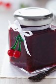 A jar of Cherry jam decorated with a bow and a fake cherry