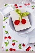Cherry-patterned place mat and card with crocheted cherries as guest favour