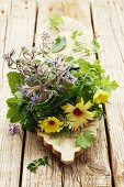 A bunch of herbs with borage and marigolds on a wooden serving dish