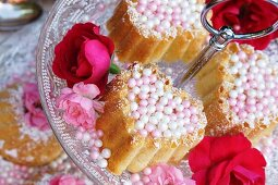 Small Bundt cakes with sugar pearls and flower decoration on a tiered cake stand