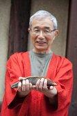 A Japanese man holding bonito and bonito flakes