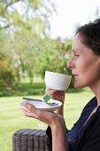 Woman drinking cup of tea on terrace in garden