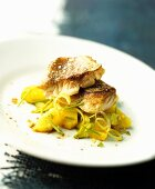 Fried fish fillets on potatoes with leek and pineapple