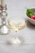 A champagne saucer, a candlestick and radishes