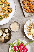 Assorted party snacks (mini spinach quiche, prawn and satay skewers, quail's eggs, radishes)