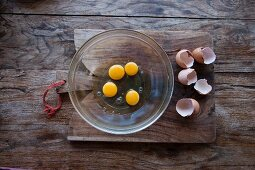 Raw eggs in a glass bowl and eggshells on a wooden board