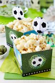 Paper boxes with football motifs being used as popcorn buckets