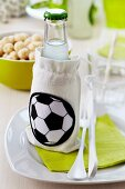 A lemonade bottle in a small fabric bag with a football decoration
