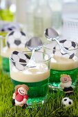 Green jelly with vanilla sauce and football decorations