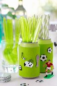 Soda cans being used as cutlery holders with football decorations