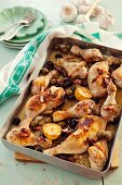 Provençal chicken legs with olives and lemons in a roasting tin