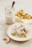 Vanillekipferl (crescent-shaped vanilla biscuits) being topped with vanilla sugar