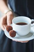 A woman holding a cup of coffee with two chocolate truffles