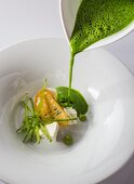 Pea soup with goat cheese and crispy sliced bread