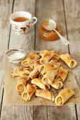 Mini apple turnovers with icing sugar and marmalade