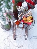 Pumpkin and leek pastries and a thermos can in a wire basket on a wooden sledge