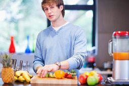 Young man in kitchen preparing fruit drink