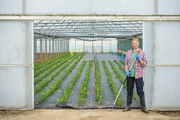 Worker standing outside polytunnel
