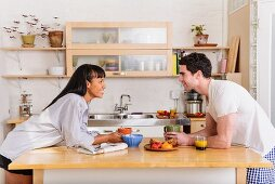 Young couple leaning on kitchen island